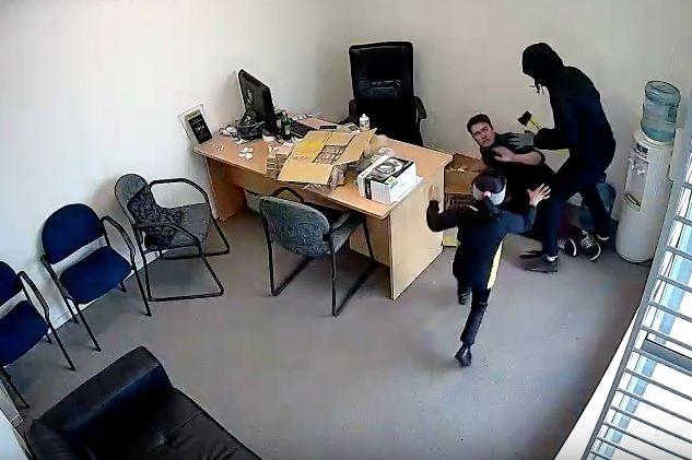 Sarah Patel runs towardtherobber as he threatens employee Jordan Byrt with an ax.