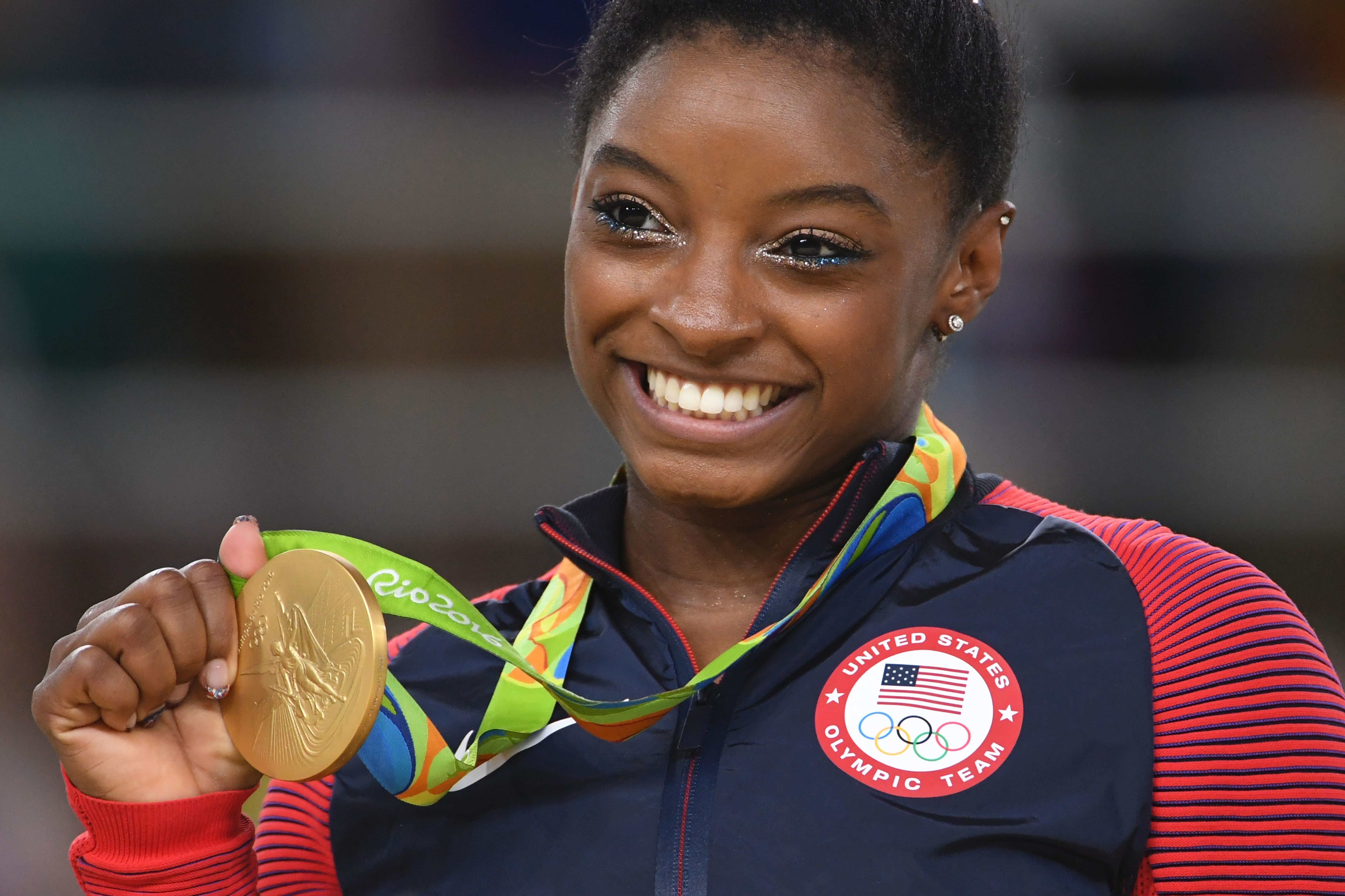 US gymnast Simone Biles celebrates on the podium of the women's floor event final of the Artistic Gymnastics at the Olympic Arena during the Rio 2016 Olympic Games in Rio de Janeiro on August 16, 2016. / AFP / Toshifumi KITAMURA        (Photo credit should read TOSHIFUMI KITAMURA/AFP/Getty Images)