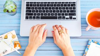 Woman's hands working at the notebook.