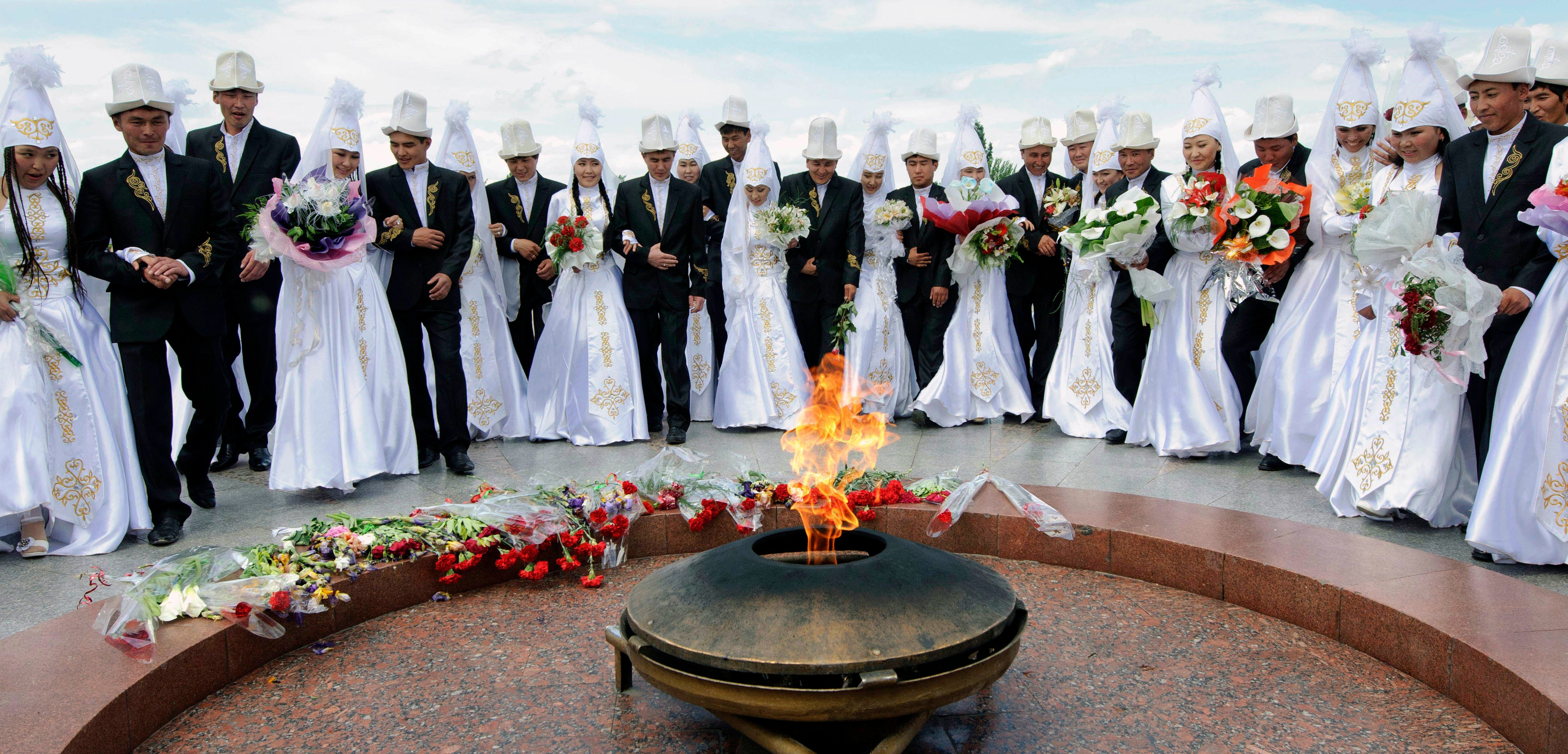 Kyrgyz brides and grooms lay flowers at the Eternal Flame before a mass wedding ceremony May 7, 2011. Some estimates say up t