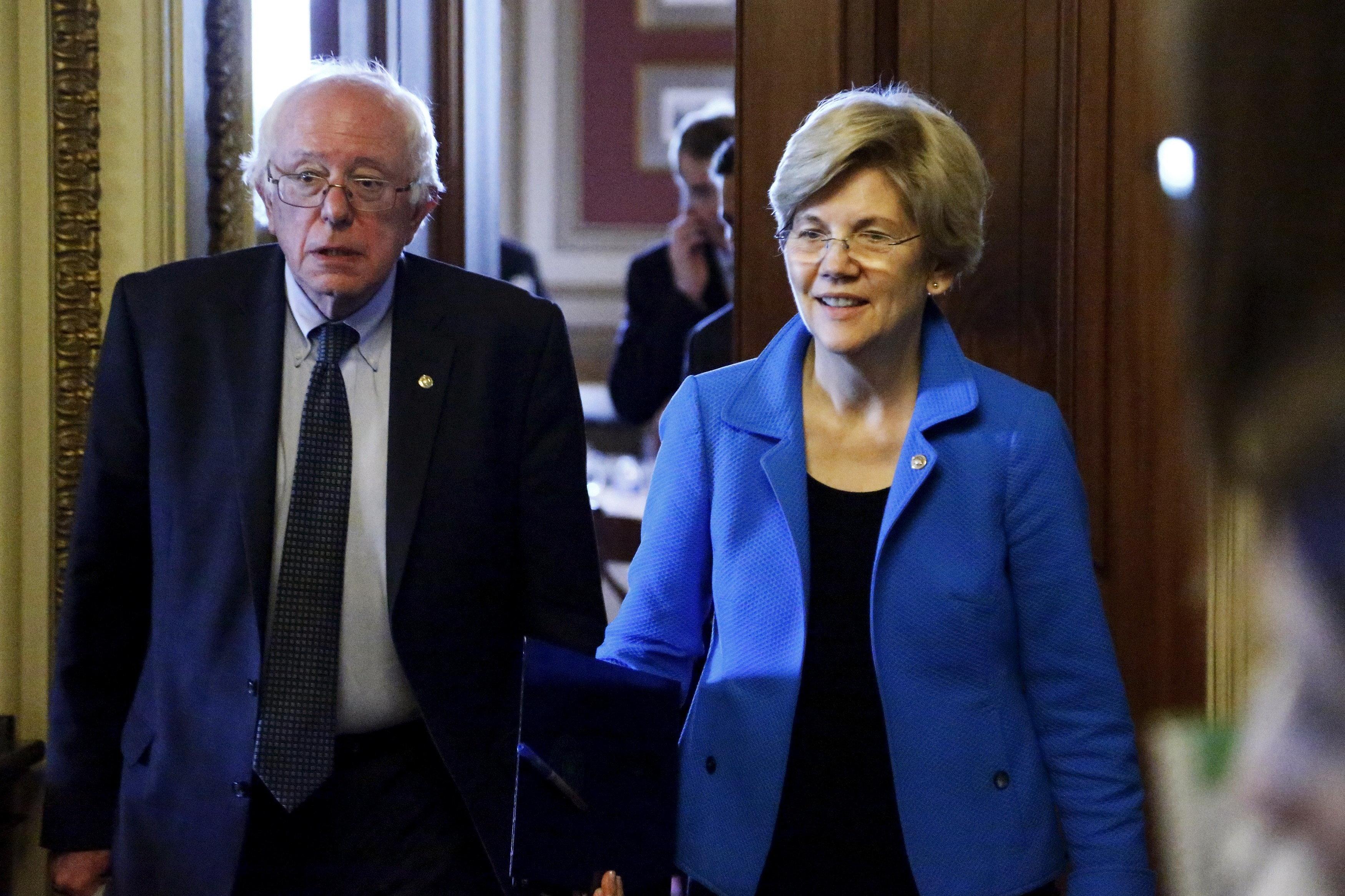 U.S. Senators Bernie Sanders (I-VT) (L) and Elizabeth Warren (D-MA) walk to the Senate floor after the weekly Democratic caucus policy luncheon at the U.S. Capitol in Washington May 12, 2015.  REUTERS/Jonathan Ernst