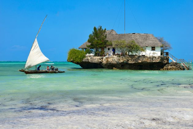 Tourist take a traditional Dhow boat to The Rock Restaurant just off Zanzibar's idyllic Bwejuu