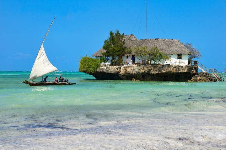 Tourist take a traditional Dhow boat to The Rock Restaurant just off Zanzibar's idyllic Bwejuu Beach.