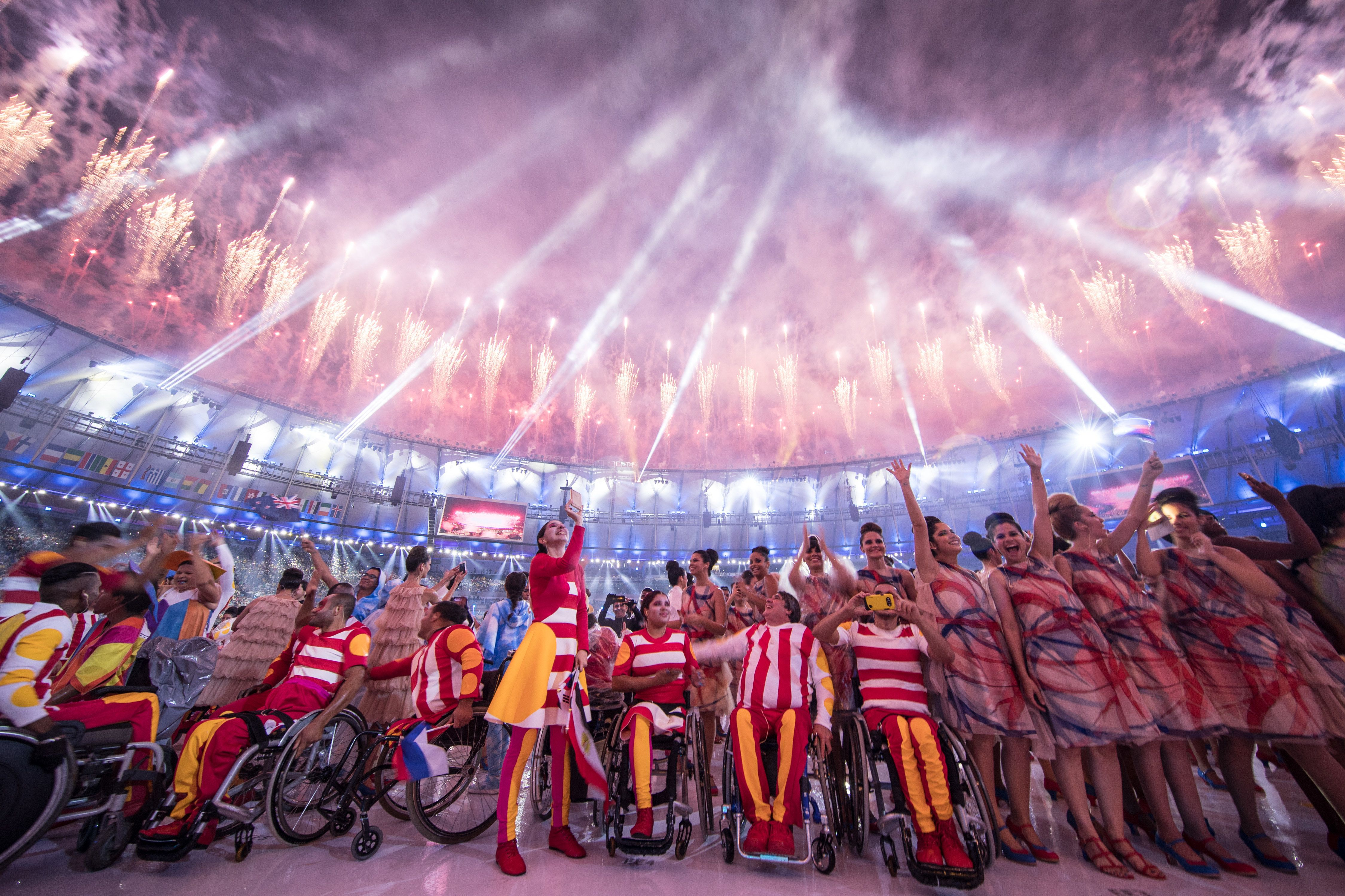 TOPSHOT - Participants react under fireworks during the opening ceremony of the Rio 2016 Paralympic Games at the Maracana stadium in Rio de Janeiro on September 7, 2016. / AFP / YASUYOSHI CHIBA        (Photo credit should read YASUYOSHI CHIBA/AFP/Getty Images)
