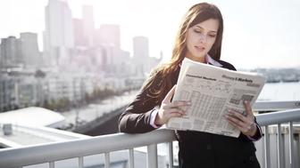 USA, Seattle, Young businesswoman reading newspaper