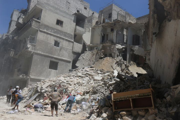 Residents inspect a damaged site after an airstrike on Aleppo's rebel-held al Mashad neighborhood in Syria on July 26.