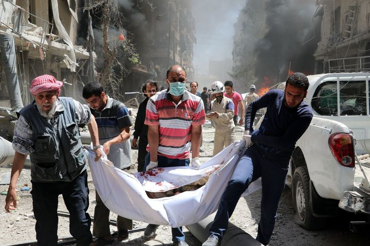 Syrians carry the body of a man after a helicopter belonging to the Syrian army carried out barrel bomb attacks on the Bayan