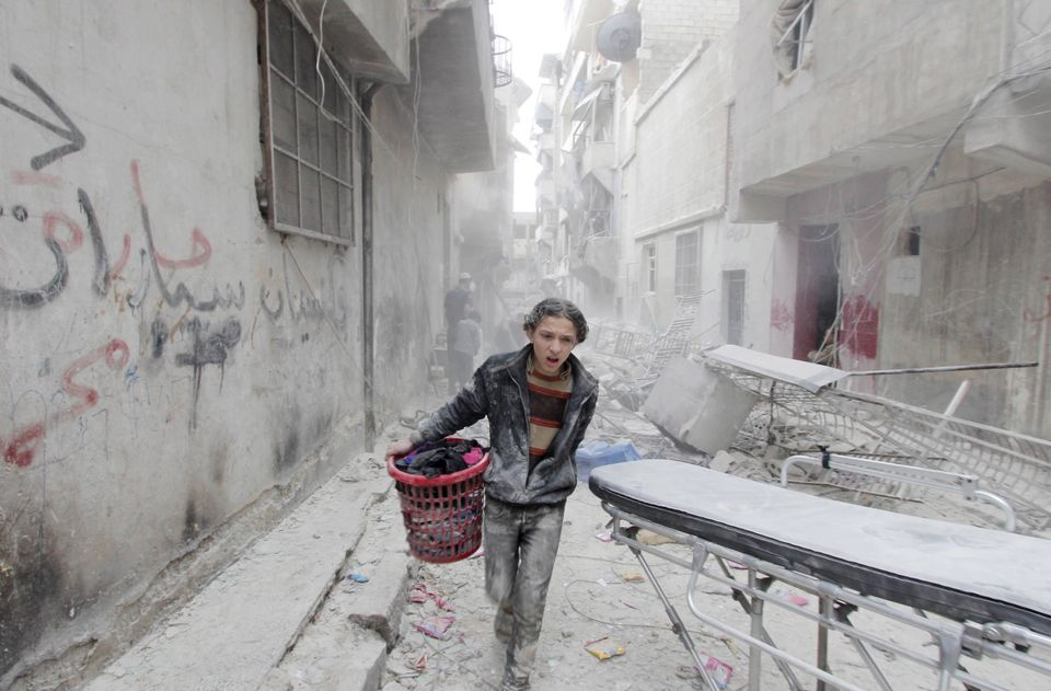 A boy carries his belongings at a site hit by what activists said was a barrel bomb dropped by forces loyal to Syria's Presid