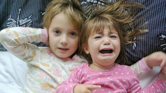 Crying little girl disturbs her sister