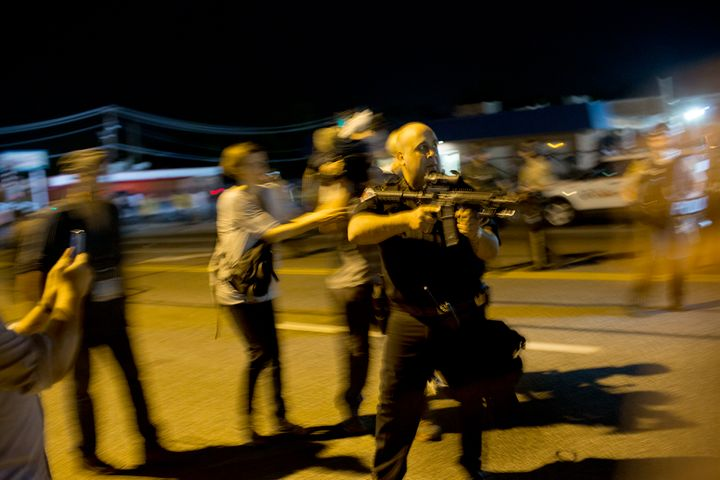 Lt. Ray Albers points his weapon at protesters on Aug. 19, 2014.