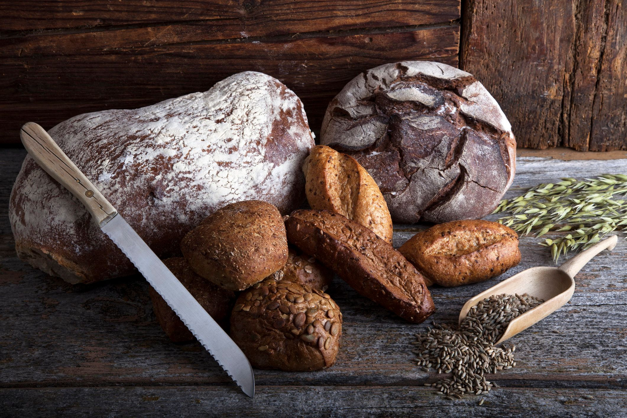 Bread loaves, rolls and a bread knife, rye grain and ears of corn on a rustic wooden surface