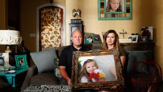 Kelly and Ryan Breaux sit holding a portrait of their deceased daughter Emma Breaux  in their home in Breaux Bridge, Louisiana, on June 16, 2016. The husband and wife lost twins, Emma and Talon, to different superbugs that they contracted while in the neonatal unit at Lafayette General Hospital. U.S.  Picture taken June 16, 2016.  TO MATCH SPECIAL REPORT USA-UNCOUNTED/SURVEILLANCE  REUTERS/Edmund Fountain