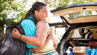 African descent boy heads off to college or moves away from home.  The 18-year-olds' mother is helping him pack up his car as he gets ready for the big move.  He is excited to start his college adventures and gives mom a big hug to say goodbye. He wears a backpack.  Family events.  Back to school.