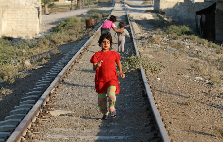 A girl walks along a broken railway track in a rebel-held neighborhood in Aleppo, Syria, on Sept. 1. The city was t