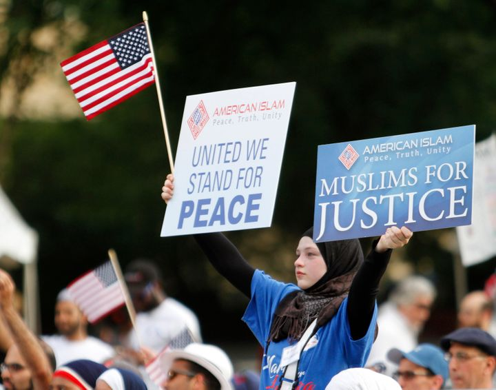A woman holds banners and a flag as she takes part in the Americans Against Terrorism, Hate and Violence rally on the National Mall in Washington, DC, on July 23, 2016.
