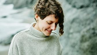 Portrait of smiling woman on beach looking down
