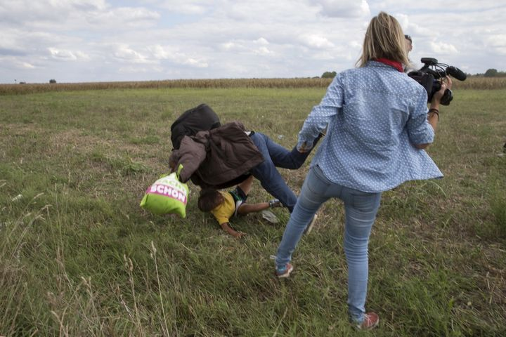 A migrant carrying a child falls near TV camerawoman (R) Petra Laszlo while trying to escape from a collection point in Roszk
