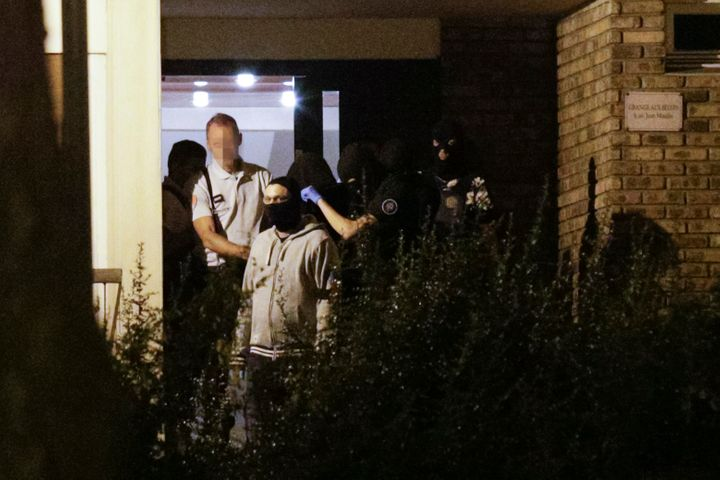 Police take a hooded woman, center,out of a building in Boussy-Saint-Antoine south of Paris on Thursday night.