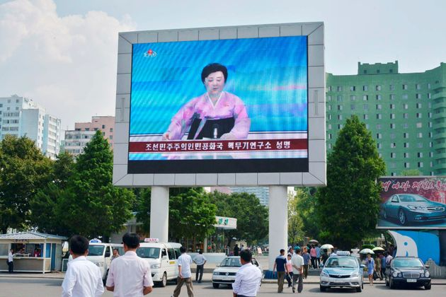 North Koreans walk past near a huge screen broadcasting the government's announcement on North Korea's...