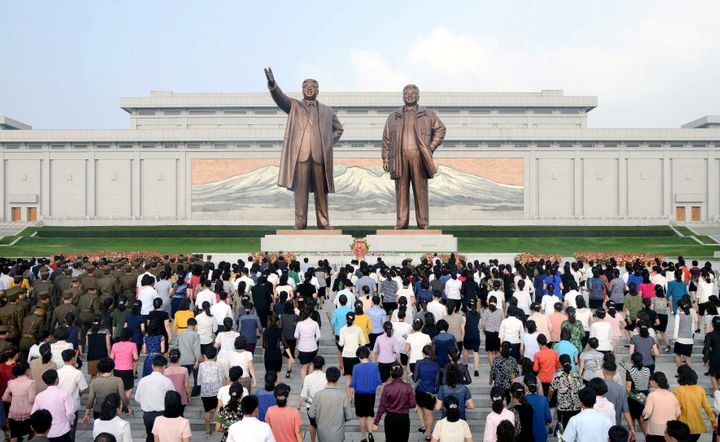 Service personnel and civilians lay floral baskets, bouquets and flowers before the statues of President Kim Il Sung and lead