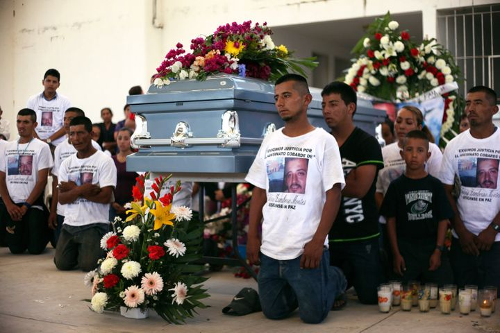 Relatives of Antonio Zambrano-Montes kneel next to his coffin during a funeral mass in Pomaro, in the Mexican state of Michoa