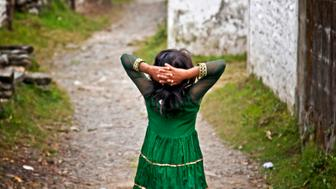 A brunette little girl in a green dress walks relaxed on a lonely stone road with the hands on her head