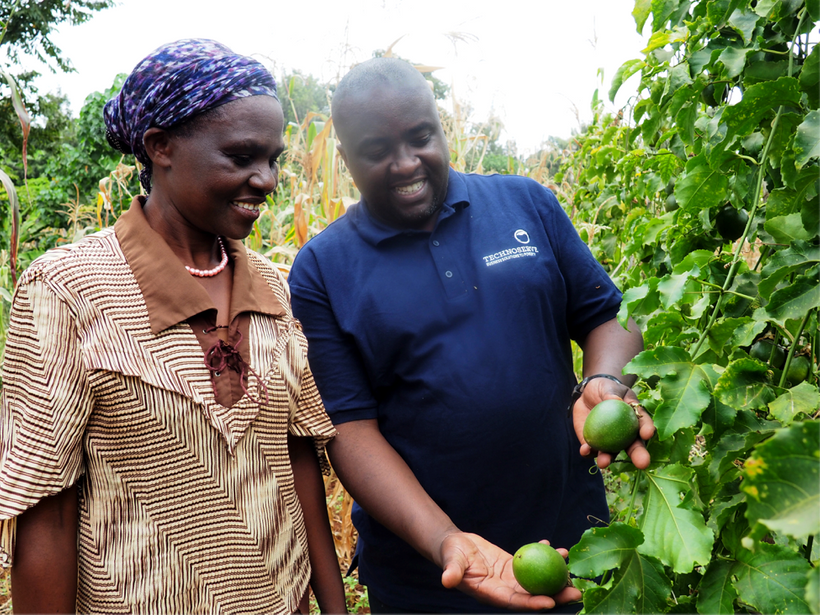 TechnoServe Project Manager Isaiah Kirema trains a passion fruit farmer in Kenya