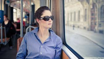 Pretty young woman wearing sunglasses and blue striped dress shirt, sitting in streetcar and looking out window at European street. City, Vienna, Austria, Europe.
