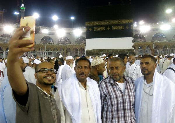 Muslim pilgrims take a selfie as they walk out following the last prayer of the day, leaving the the Grand Mosque in the Saud