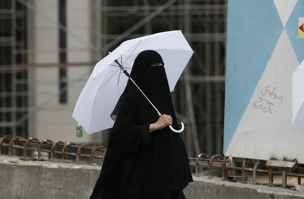 A Muslim pilgrim holds a parasol as she walks in the streets of Saudi Arabia's holy city of Mecca on Sept. 6.