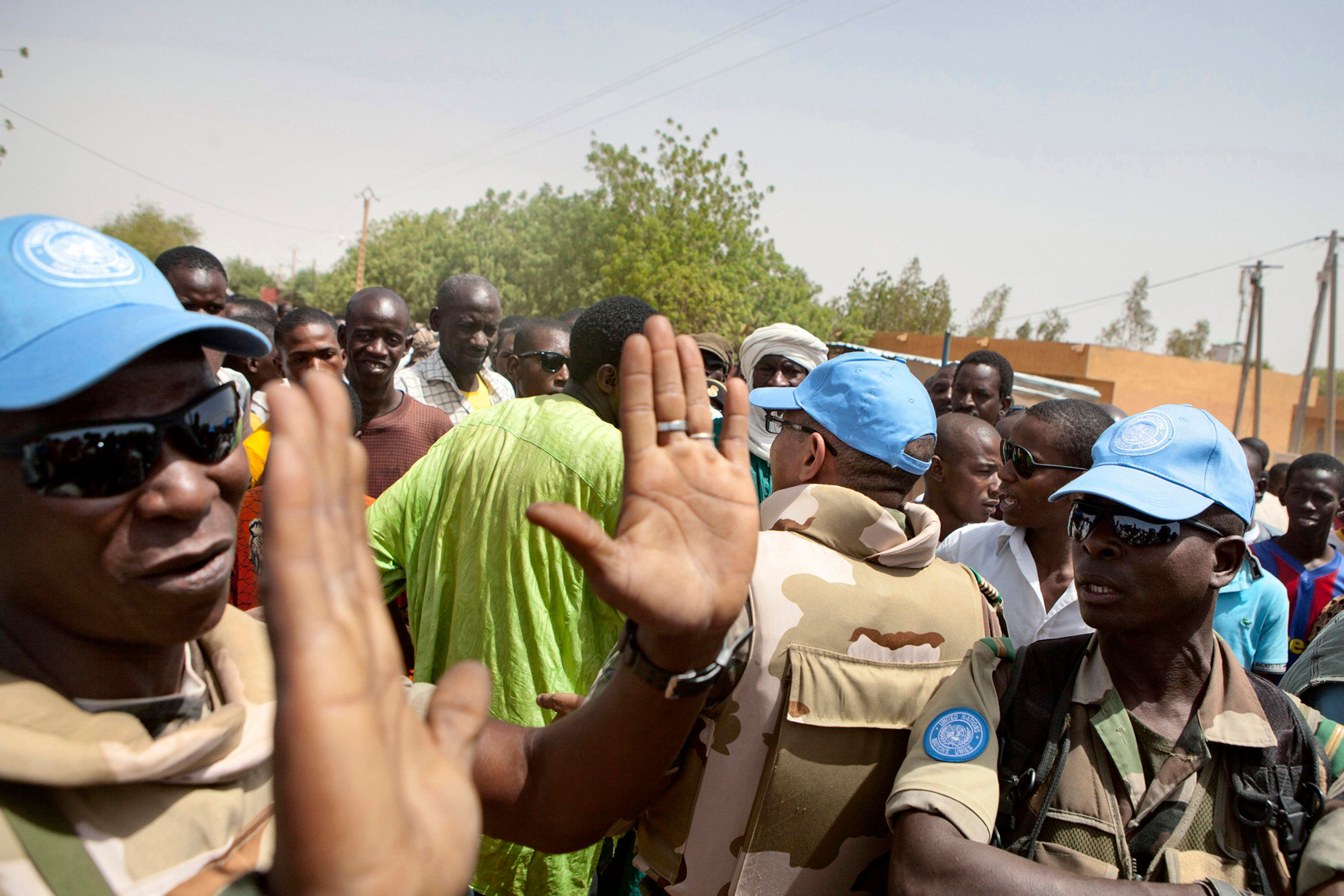 United Nations peacekeepers try to calm a crowd during a protest against sending peacekeepers from Senegal to the northern re