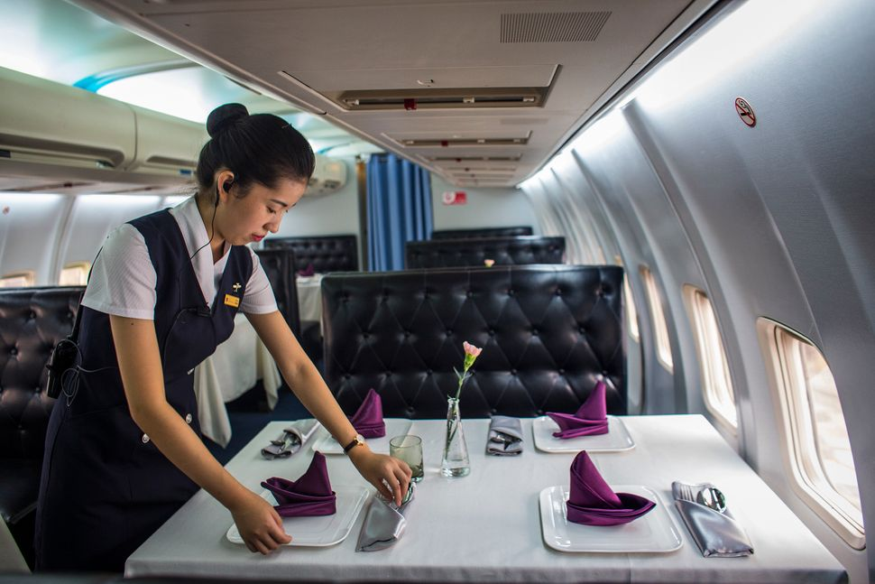 Awaitress puts finishing touches on a table inside China's first airplane restaurant.
