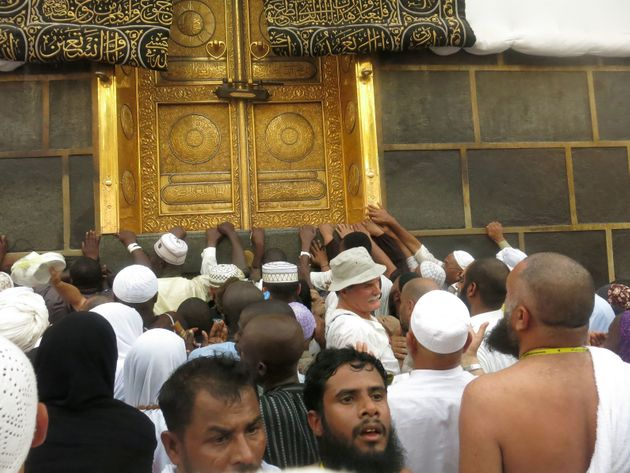 Muslim pilgrims touch the golden doors of the Kaaba, Islam's holiest shrine, at the Grand Mosque in Saudi...