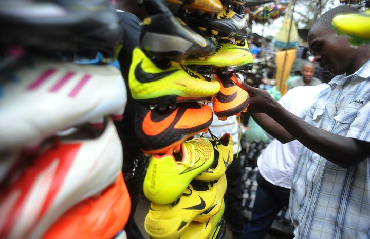 A shopper looks at football shoes displayed in Gikomba Market, East Africa's biggest secondhand clothing market, on July 10,