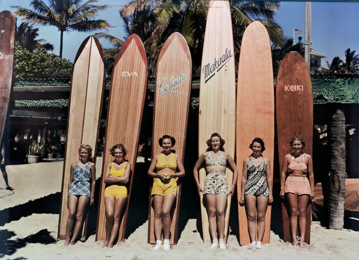 Women pose in front of surfboards on Waikiki Beach in Honolulu, Hawaii, in a photo from a 1938 issue of National Geographic. Their bare beach legs are very contemporary—a couple of decades prior, they might have been wearing stockings.
