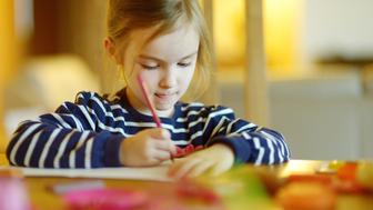 Cute little girl is drawing with pencils in preschool