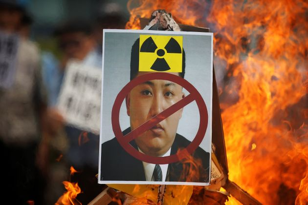 A cut-out of North Korean leader Kim Jong Un is set on fire during an anti-North Korea rally in central...