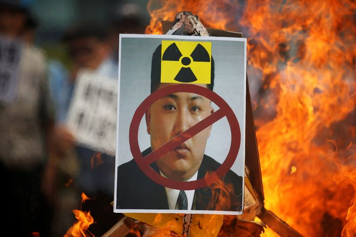 A cut-out of North Korean leader Kim Jong Un is set on fire during an anti-North Korea rally in central Seoul, South Korea, o