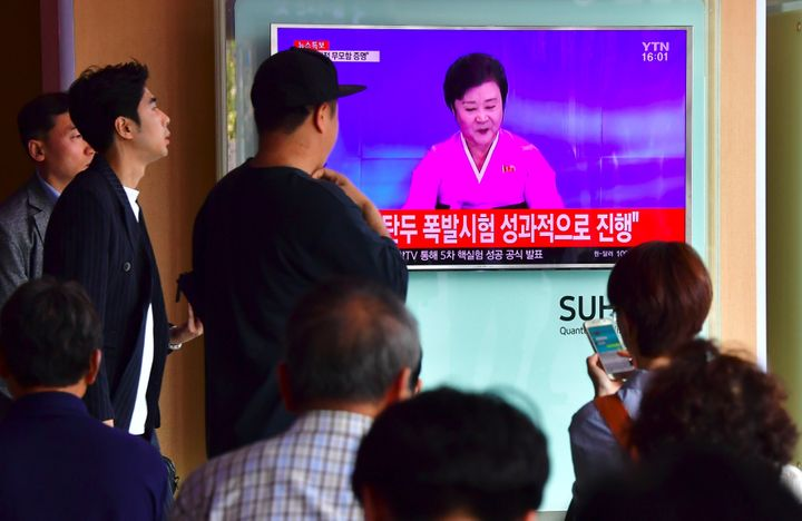 People watch a television news broadcast showing a North Korean anchor announcing the country's latest nuclear test carried o