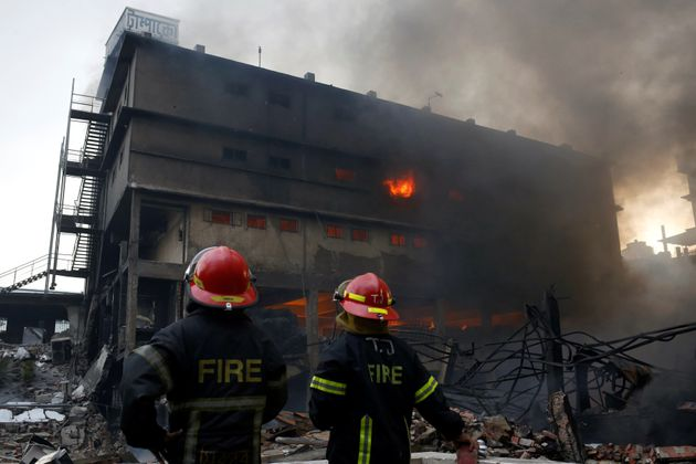 Firefighters stand at the site of a fire at a packaging factory outside Dhaka, Bangladesh, September...