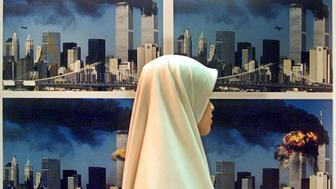 A Malaysian Muslim woman walks past a display of photos showing United Airlines flight 175 crashing into the World Trade Center South Tower at a gallery in Kuala Lumpur September 25, 2002. Two hundred award-winning images taken in 2001 are currently on display in Malaysia's National Art Gallery. The background photos in this image were taken by U.S. photographer Robert Clark. REUTERS/Bazuki Muhammad  BM/PB