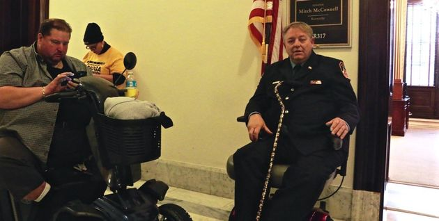 Kenny Anderson and Ray Pfeifer wait outside Mitch McConnell's office hoping to plead for his help passing...