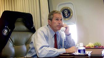 US President George W. Bush talks on the phone with New York Mayor Rudy Guiliani and Gov. George Pataki aboard Air Force One. Bush gave a statement about the two planes that crashed into the World Trade Center in New York City and one that crashed into the Pentagon in Washington DC earier 11 September. AFP PHOTO  (Photo credit should read DOUG MILLS/AFP/Getty Images)