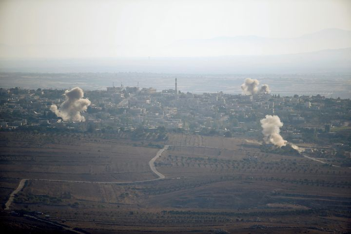 Smoke from explosions rises during fighting in the village of Jubata Al Khashab, held by Syrian rebel groups fighting to over