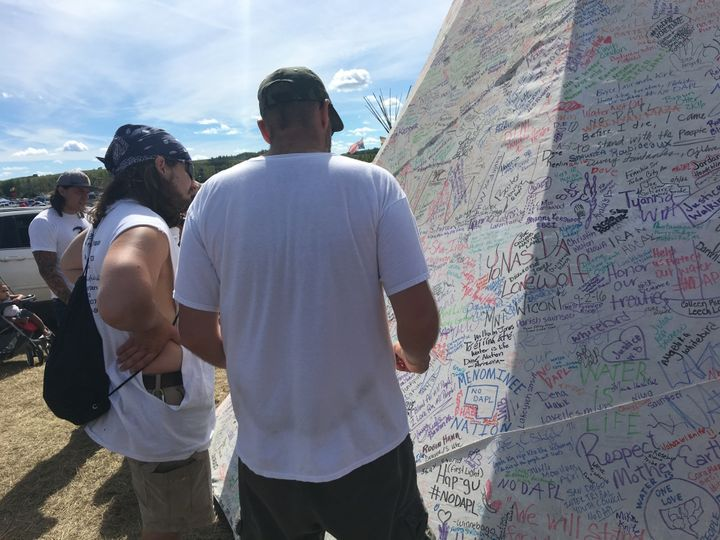 A teepee near the protests is covered in signatures and messages of support.