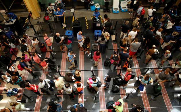 Passengers make their way through a TSA checkpoint at Reagan National Airport at the start of the Independence...