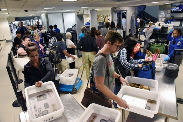 Delayed passengers inside Terminal 7 at Los Angeles International Airport line up to go through TSA security...