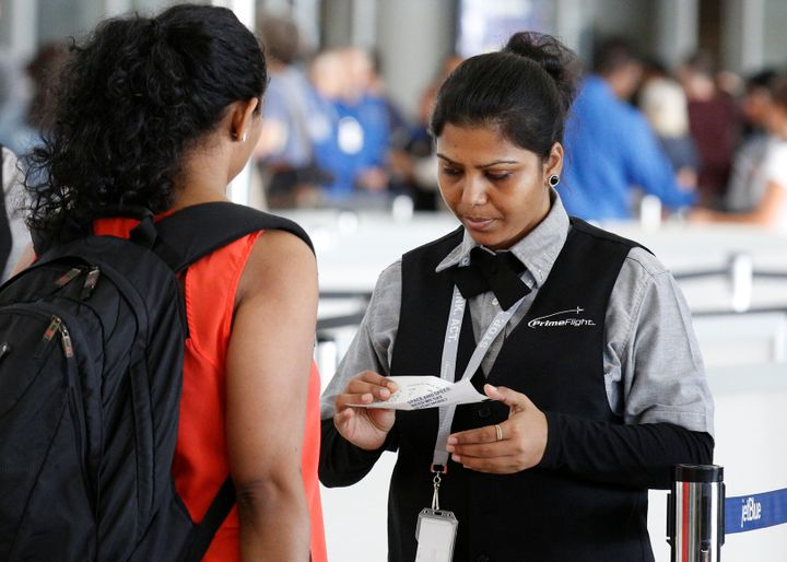 An airport private contractor prepares a passenger at a security checkpoint during the check-in process at JFK airport i