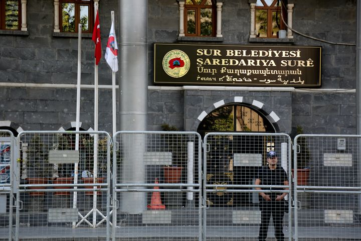 A riot police officer stands guard in front of Sur municipality office, following the removal of the local mayor from office