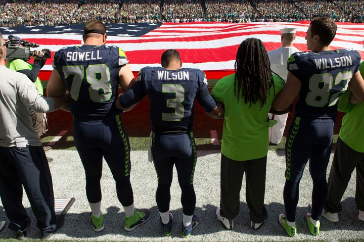 Seattle Seahawks join arms during the national anthem before their game against the Miami Dolphins.